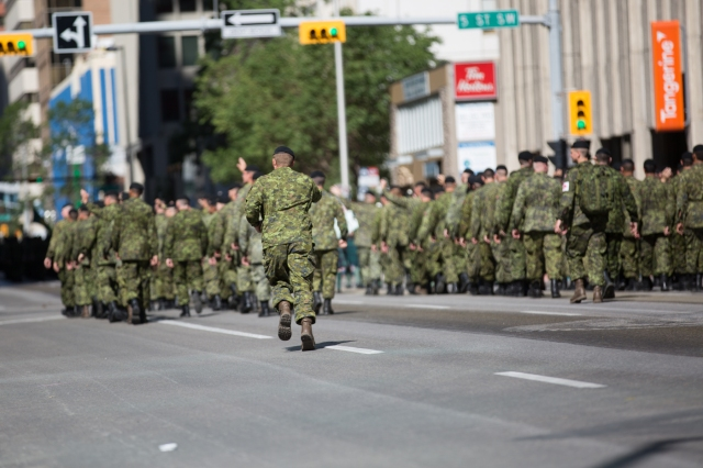A soldier caught up in crowd recognition runs back to his platoon at the Calgary Stampede. © J. Ashley Nixon