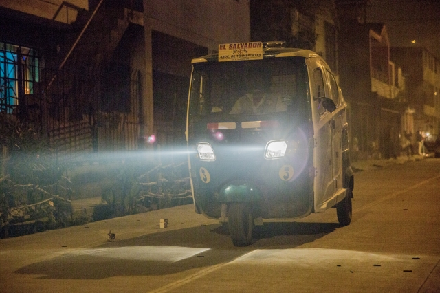The lights of a mototaxi (three wheeler bike with driver and 2/3 passengers) cuts through the smoke-filled streets of Villa El Salvador, Lima