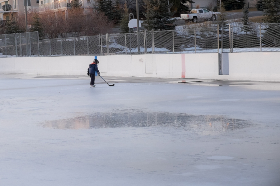A lone skater stick handles between the puddles. Battalion Park Outdoor Arena, Calgary, Canada. © J. Ashley Nixon