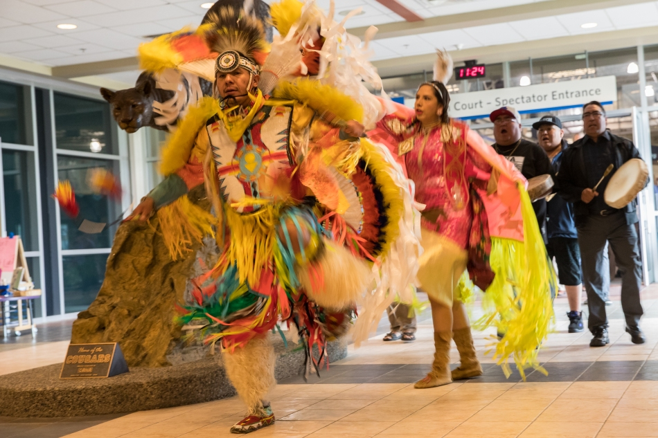 Dancers and drummers from the Niits (Blackfoot First Nation) lead a parade of students past The Cougars statue and through the corridors of Mount Royal University