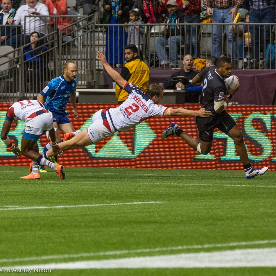 2 on 2. Fiji's Jasa Veremalua makes it to the try line despite Ben Pinkelman's superman heroics for USA in the HSBC Rugby Sevens at BC Place, Vancouver. © J. Ashley Nixon