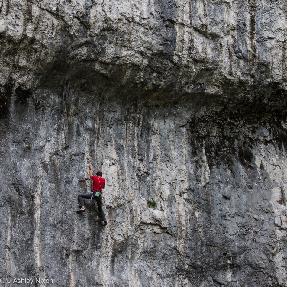Rock climber on the limestone face of Malham Cove, Yorkshire Dales National Park, Yorkshire, England. July 8, 2016. © J. Ashley Nixon