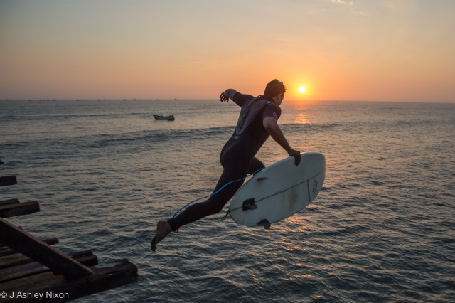 Alonso, a local surfer, jumps off the pier at Pimentel, Peru into the sun and the Pacific Ocean. Aug 25, 2016. © J. Ashley Nixon