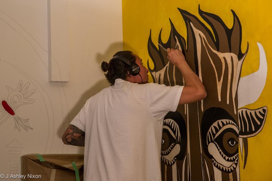 Indigenous (Blackfoot) artist, Ryan Jason Allen Willert HeavyShield, working on his painting of the buffalo at Mount Royal University, Calgary, Canada. © J. Ashley Nixon
