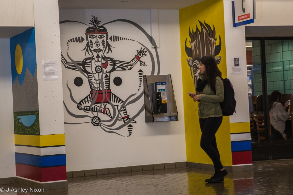 A student walking along Main Street checks out the paintings of Indigenous (Blackfoot) artist, Ryan Jason Allen Willert HeavyShield at Mount Royal University, Calgary, Canada. © J. Ashley Nixon