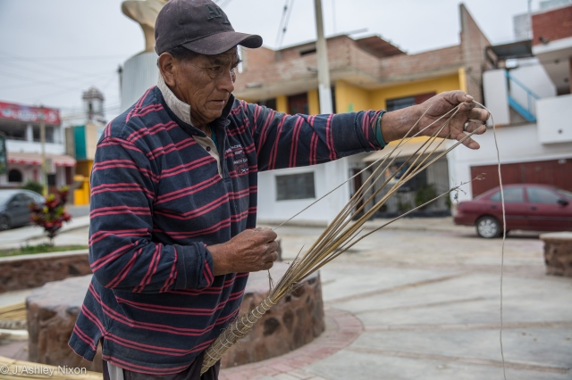 José, fisherman of Huanchaco, Peru constructing a traditional reed boat (Caballito de Totora) on the street. © J. Ashley Nixon