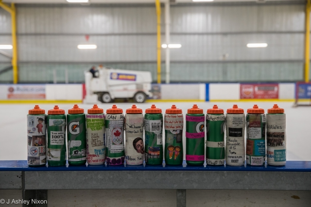 Water bottles lined up on the bench after the Girls hockey final at Max Bell Arena between Calgary Girls Hockey White and Silver teams in the Esso Minor Hockey Week tournament, Calgary, Alberta, Canada. © J. Ashley Nixon