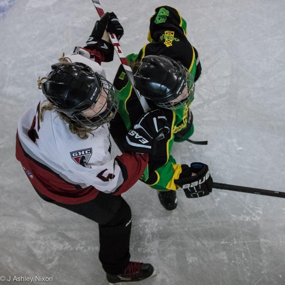 Hockey action along the boards between Calgary Girls Hockey Bantam 1 White Hawks and Okotoks at Stavely Arena, Alberta. © J. Ashley Nixon