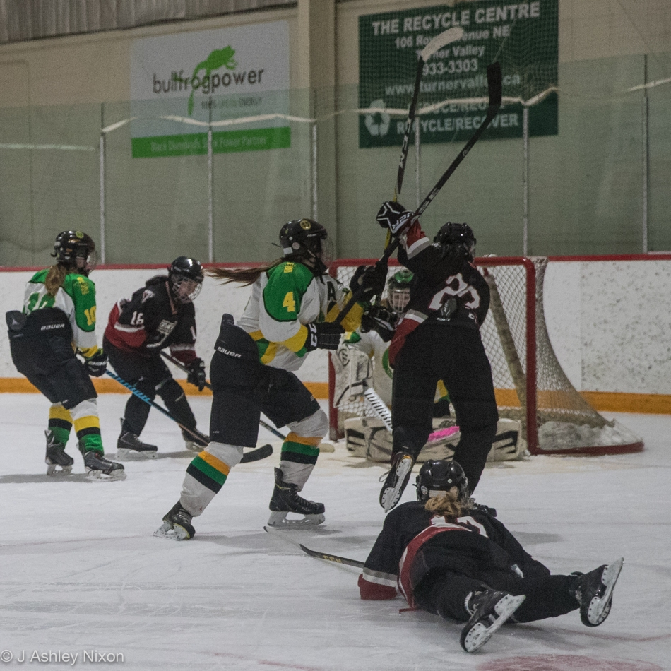 Carolyn Berze flies through the air to score the second of three goals in a minute for the Calgary Girls Hockey Bantam White Hawks against the Okotoks Oilers in the first round of the Calgary City hockey championships in Black Diamond, Alberta, Canada. © J. Ashley Nixon